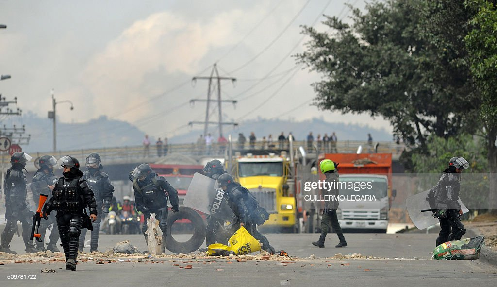 Riot police dismantle a roadblock during a protest at the 'Transmilenio' station in southern Bogota, Colombia, on February 12, 2016. Users of public transportation blocked roads to protest what they consider poor service and high cost. Amid the protest several buses were damaged as well as stations destroyed and several demonstrators were detained by police after clashes. AFP PHOTO / GUILLERMO LEGARIA / AFP / GUILLERMO LEGARIA
