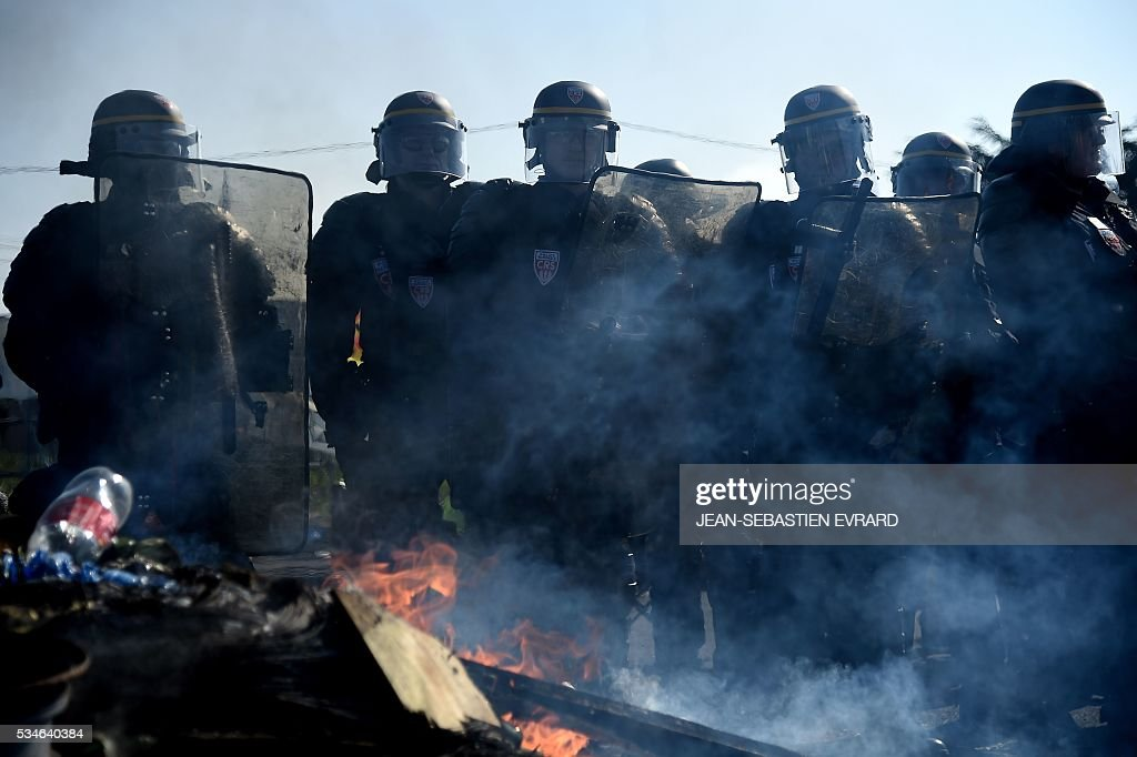 Riot police evacuates striking workers who block the access to an oil depot near the Total refinery of Donges, western France, on May 27, 2016 to protest against the government's planned labour law reforms. France's Socialist government has bypassed parliament and rammed through a labour reform bill that has sparked two months of massive street protests.protests. / AFP / JEAN