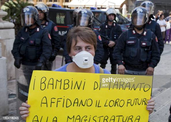 Riot Police face residents and workers of the Ilva steelworks during a protest against pollution during a demonstration in the Italian southern city...