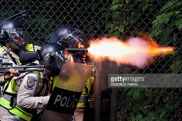TOPSHOT Riot police fire rubber bullets and tear gas grenades at students from the public Central University of Venezuela who demonstrate in demand...