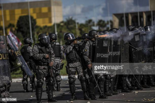 Riot police fire rubber bullets at demonstrators during protests outside of the National Congress demanding the resignation of President Michel Temer...