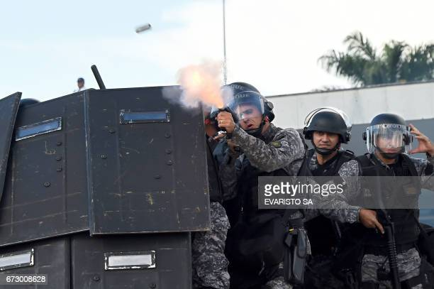 TOPSHOT Riot police fire tear gas at Brazilian indigenous people from diverse ethnic groups during the annual march for their rights in Brasilia on...