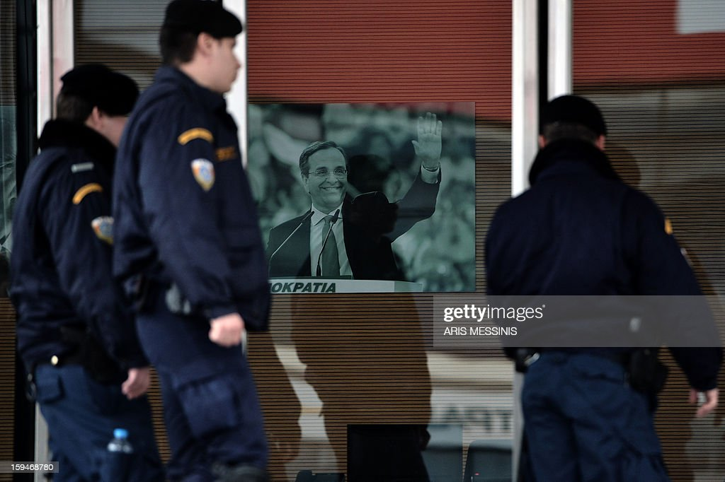 Riot police foce walk on January 14,2013 past a portrait of Greek Prime Minister and leader of the conservative party New Democracy Antonis Samaras as they enter the party's headquarters in Athens. Shots were fired early on January 14 near the offices of main Greek ruling party New Democracy in Athens, police said, after a recent wave of arson attacks against political offices. AFP PHOTO / ARIS MESSINIS