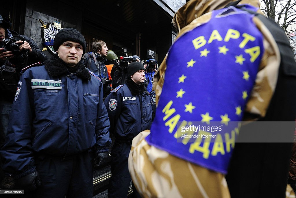 A riot police force officer watches an anti-government protester wearing an Europian Flag on his arm during a rally on Instytutska Street on February 14, 2014, in Kiev, Ukraine. According to Opposition Officals, Berkut police forces could attack the barricades any moment; protesters have gathered inside and prepared fireworks and molotov-cocktails. Media and other people were removed from the barricades. Russian Foreign Minister Sergei Lavrov again issued a warning to the West against interfering in Ukraine's political crisis during today's joint press conference with German federal foreign Minister Walter Steinmeier, who is on a two-day visit to Russia. According to reports Ukrainian opposition leaders Vitaly Klitschko and Arseny Yatsenyuk are set to meet with German Chancellor Angela Merkel on February 18, 2014 in Germany.