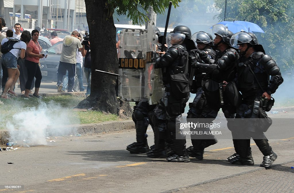 Riot police forces use tear gas against natives and people who support native cause during a their protest against the eviction of natives outside the former Indigenous Museum --aka Aldea Maracana-- next to the Maracana stadium in Rio de Janeiro, Brazil on March 22, 2013. Indigenous people have been occupying the place since 2006, which is due to be pulled down to construct a parking lot for the upcoming Brazil 2014 FIFA World Cup. AFP PHOTO/VANDERLEI ALMEIDA