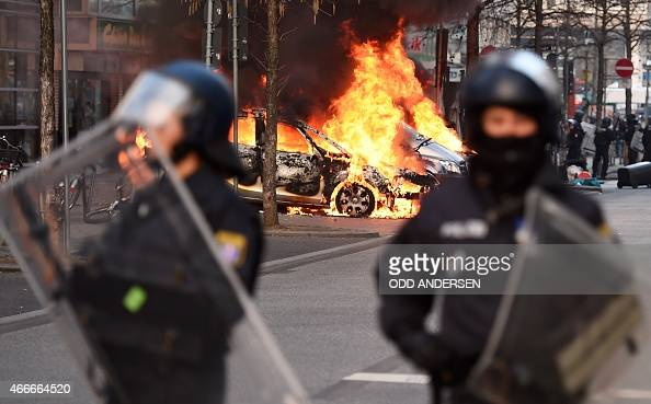 Riot Police form a cordon as a Police car burns on the opening day of the European Central Bank in Frankfurt am Main western Germany on March 18 2015...