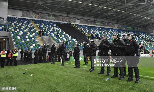 Riot police form a line on the playing surface after crowd disorder during the Champions League second round first leg qualifying game between...