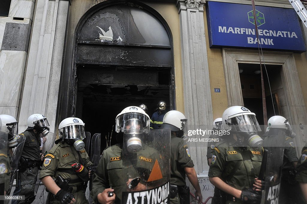 Riot police guard a burnt branch of the Marfin Bank in Athens after a violent demonstration on May 5, 2010. Athens police chiefs mobilized all their forces, including those not on active duty, to restore order on May 5 amid rioting during protests against a government austerity drive. Police were put on a 'general state of alert' to deal with the clashes after three people died in the bank that was firebombed on the margins of the demonstrations. AFP PHOTO / Aris Messinis