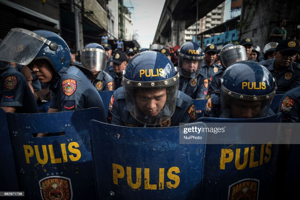 """Riot police hold formation as protesters hold a demonstration against President Rodrigo Duterte in Manila, Philippines, November 30, 2017. Thousands of President Duterte's critics staged protests to condemn his plan of setting up a """"revolutionary government"""", fearing it may lead to a dictatorship. The protests come after President Duterte ordered government troops to eliminate communist rebels and left-wing groups, labelling them as terrorists. Ezra Acayan/NurPhoto"""