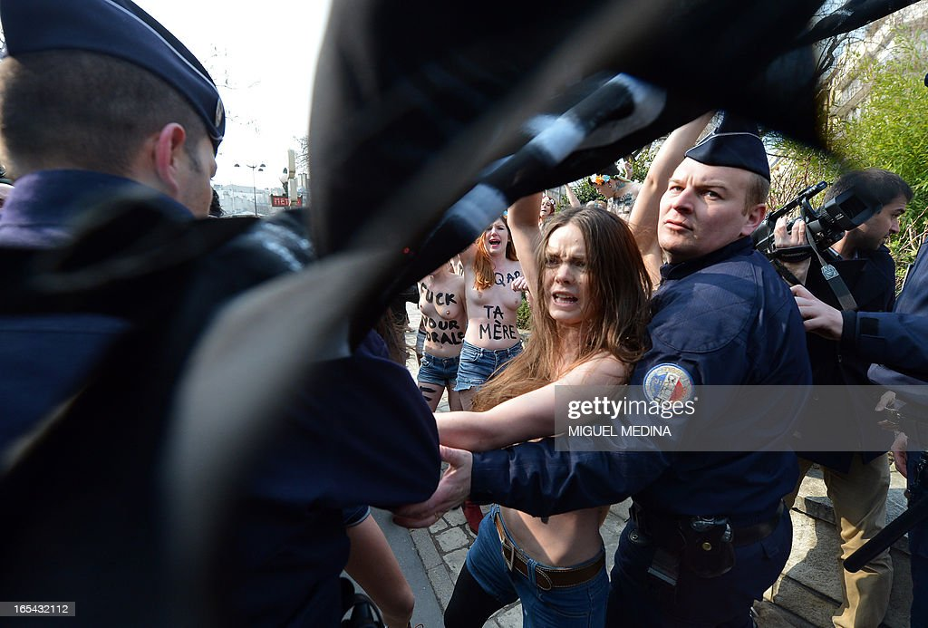 Riot police intervene during a a topless protest by activists of the women's rights movement Femen near Tunisia's Embassy in Paris on April 4, 2013. Femen called for a day of international 'topless jihad' on April 4 with Femen groups staging protests in various European cities in support of Amina, a young Tunisian woman who caused a scandal when she published photos of herself bare-chested on the internet in March.