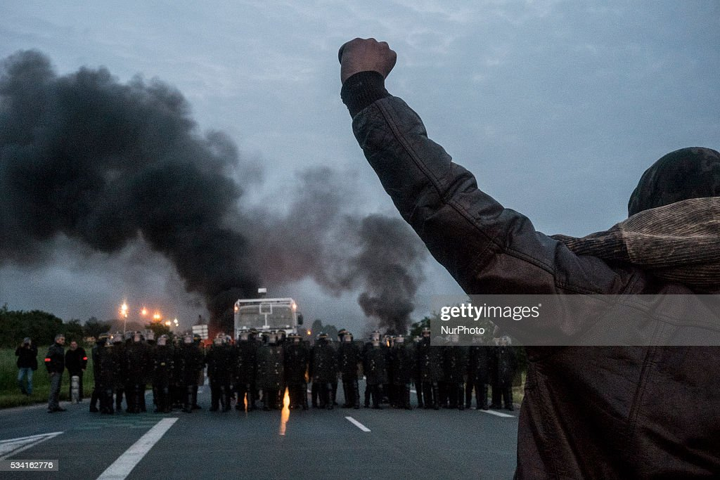 Riot police intervene to disperse refinery worker holding a blockade of the oil depot of Douchy-Les-Mines to protest against the government's proposed labour reforms, on May 25, 2016. Refinery workers stepped up strikes that threaten to paralyse France weeks ahead of the Euro 2016 tournament as the government moved to break their blockades, escalating a three-month tug-of-war over labour reforms.