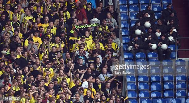 Riot police is seen next to fans of Dortmund during the Bundesliga match between FC Schalke 04 and Borussia Dortmund at Veltins Arena on September 27...