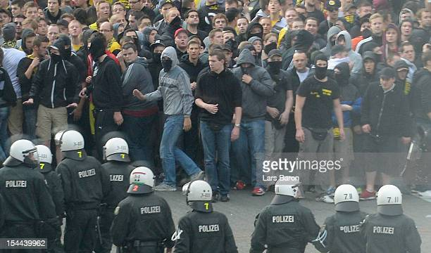 Riot police is seen next to fans of Dortmund prior to the Bundesliga match between Borussia Dortmund and FC Schalke 04 at Signal Iduna Park on...