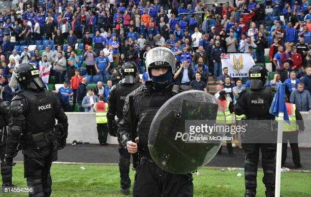 Riot police line up in front of the Linfield fans after crowd disorder during the Champions League second round first leg qualifying game between...