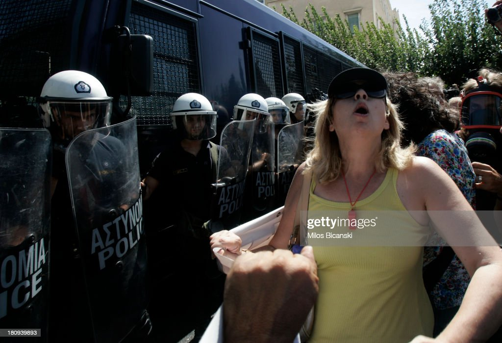 Riot police look on as a protestor shouts support during a demonstration against austerity and job cuts on September 18, 2013 in Athens, Greece. As part of the redeployment plan in the country reeling from six years of recession, civil servants have to accept new posts or spend eight months on reduced salaries as alternative posts are found, with the risk of losing their jobs altogether.