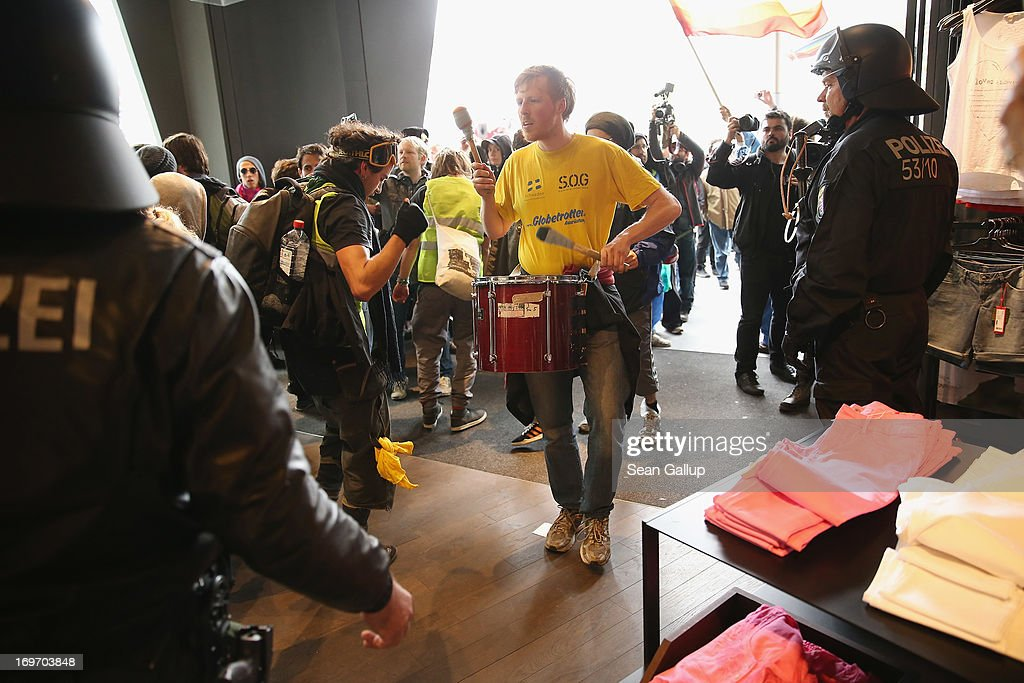 Riot police look on shortly before evicting Blockupy protesters who had stormed into a clothing store in the Zeil pedestrian shopping street on May 31, 2013 in Frankfurt am Main, Germany. Several thousand protesters are taking part in Blockupy protests today and tomorrow in Frankfurt in order to demonstrate aginst ECB debt policy, food prices speculation by Deutsche Bank and the labor practices inherent in the discount clothing industry.