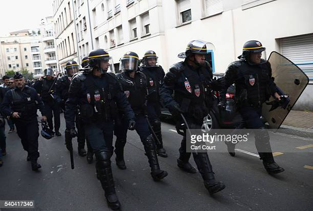 Riot police march through the street to provide backup to officers during clashes with fans on June 15 2016 in Lille France Football fans from around...