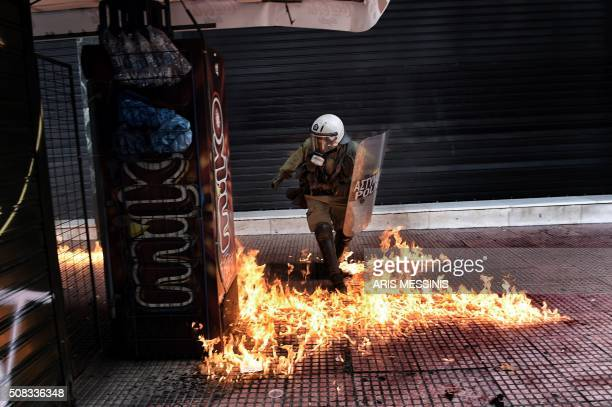 TOPSHOT A riot police member walks through fire during a massive protest beside the Greek parliament during a massive protest on February 4 2016...