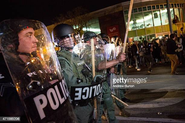 Riot police monitor protesters near a CVS pharmacy that was looted and burned by rioters on Monday after the funeral of Freddie Gray on April 29 2015...