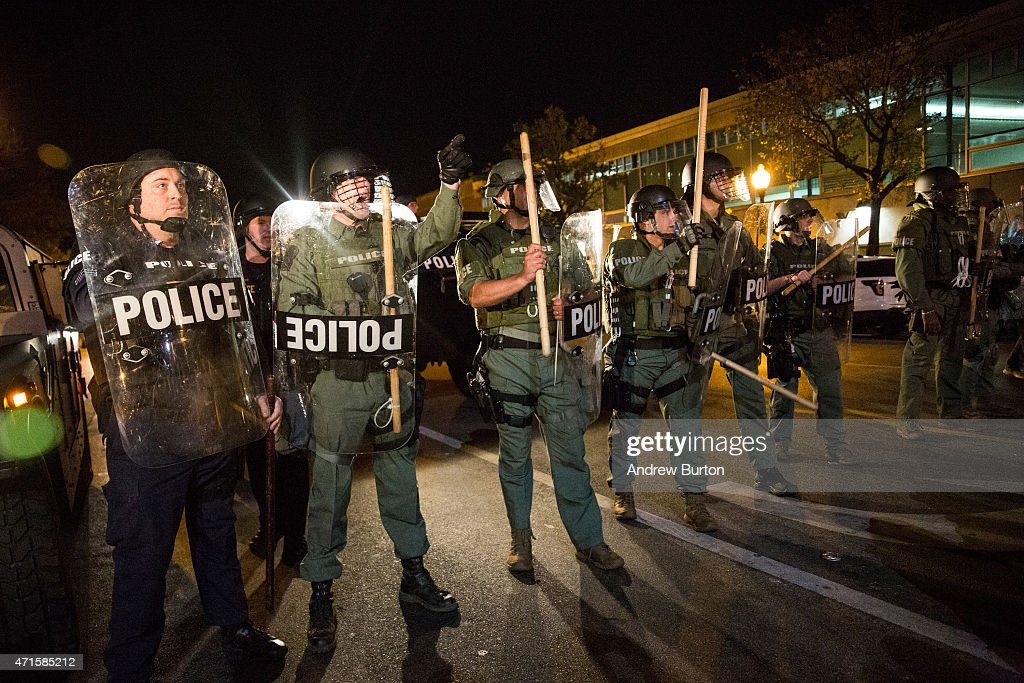 Riot police monitor protesters near a CVS pharmacy that was looted and burned by rioters on Monday after the funeral of Freddie Gray, on April 29, 2015 in Baltimore, Maryland. Gray, 25, was arrested for possessing a switch blade knife April 12 outside the Gilmor Houses housing project on Baltimore's west side. According to his attorney, Gray died a week later in the hospital from a severe spinal cord injury he received while in police custody.