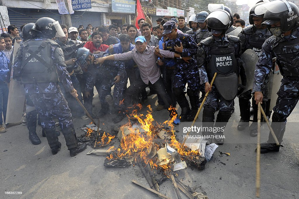 Riot police move in as Nepalese student activists burn an effigy of Lokman Singh Karki after his appointment as Commission for the Investigation of Abuse of Authority chief in Kathmandu on May 9, 2013. Dozens of rights activists and student organisations have been protesting since the start of the week over the Constitutional Council's decision to appoint Lokman Singh Karki to run the Commission for the Investigation of Abuse of Authority. AFP PHOTO/ Prakash MATHEMA