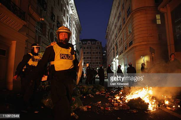 Riot police move in front of a burning barricade in Jermyn Street during clashes with protesters after a march in protest against government cuts on...