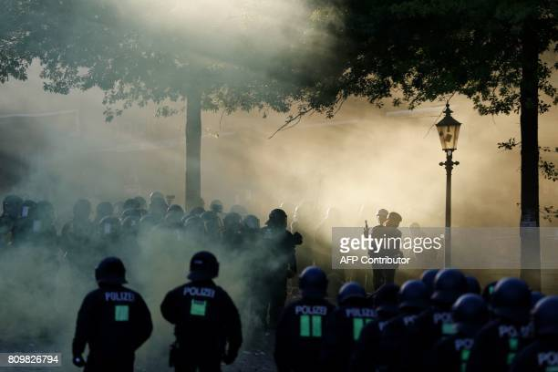 TOPSHOT Riot police move in through the smoke from a smoke bomb during the 'Welcome to Hell' rally against the G20 summit in Hamburg northern Germany...