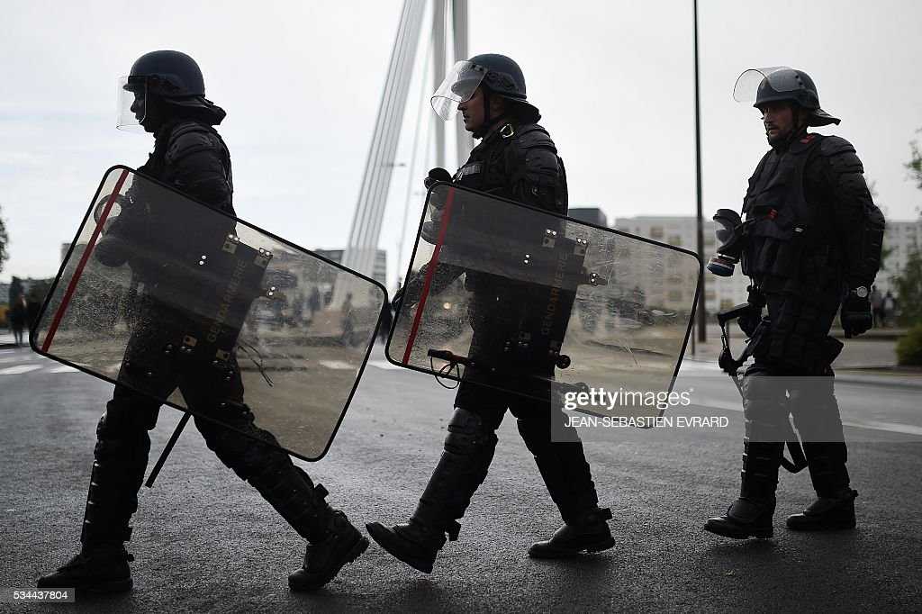 Riot police move into position on May 26, 2016 in Nantes, western France, during a protest against government planned labour law reforms. The French government's labour market proposals, which are designed to make it easier for companies to hire and fire, have sparked a series of nationwide protests and strikes over the past three months. Masked youths clashed with police and striking workers blockaded refineries and nuclear power stations on May 26 as an escalating wave of industrial action against labour reforms rocked France. / AFP / JEAN