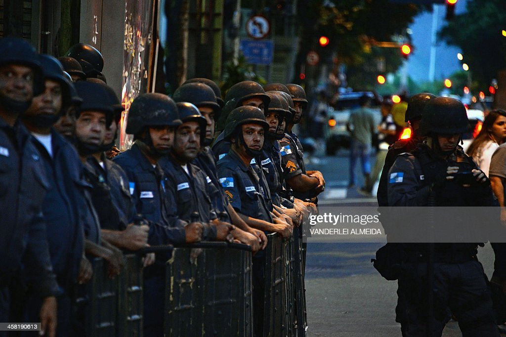 Riot police observe demonstrators taking part in a protest against a public transport fare hike announced for January 2014 by Rio de Janeiro's Mayor Eduardo Paes, in the streets of the Brazilian city, on December 20, 2013.