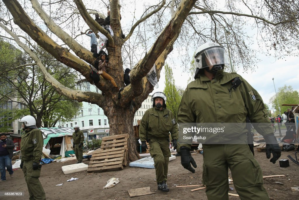Riot police occupy the site of the former temporary refugee camp while protesters watch from a tree at Oranienplatz in Kreuzberg district on April 8, 2014 in Berlin, Germany. Several hundred riot police sealed off the square after, according to an eyewitness, violence broke out between refugees who had accepted a deal by the city to leave the camp and a small number who insisted on staying. Refugees, many of them from Africa who came to Germany via Lampedusa, began dismantling their shelters today after many of them agreed to a deal with city authorities to move to a renovated hostel. Not all of the several hundred refugees, some of whom have been living at the Oranienplatz camp almost a year, have agreed to the deal, and while some said they will go elsewhere, some insisted they will stay, despite a city order to vacate.