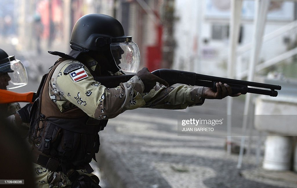A riot police officer aims its gun as protesters block an access to the Arena Fonte Nova Stadium in Salvador, Bahia --where Nigeria is to play Uruguay in a FIFA Confederations Cup Brazil 2013 football match-- during a protest of what is now called the 'Tropical Spring' against corruption and price hikes. Brazilians took to the streets again Thursday in several cities on a new day of mass nationwide protests, demanding better public services and bemoaning massive spending to stage the World Cup. More than one million people have pledged via social media networks to march in 80 cities across Brazil, as the two-week-old protest movement -- the biggest seen in the South American country in 20 years -- showed no sign of abating.