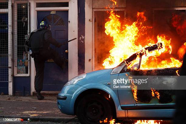 A riot police officer attempts to break down the door of a house next to a burning car as he is targeted by rioters after local residents claimed a...
