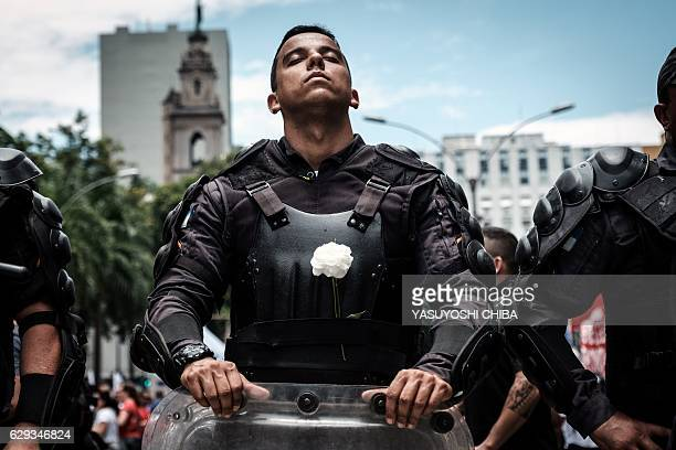 TOPSHOT A riot police officer bearing a white flower on his bulletproof vest takes part in a public servants' protest against austerity measures in...