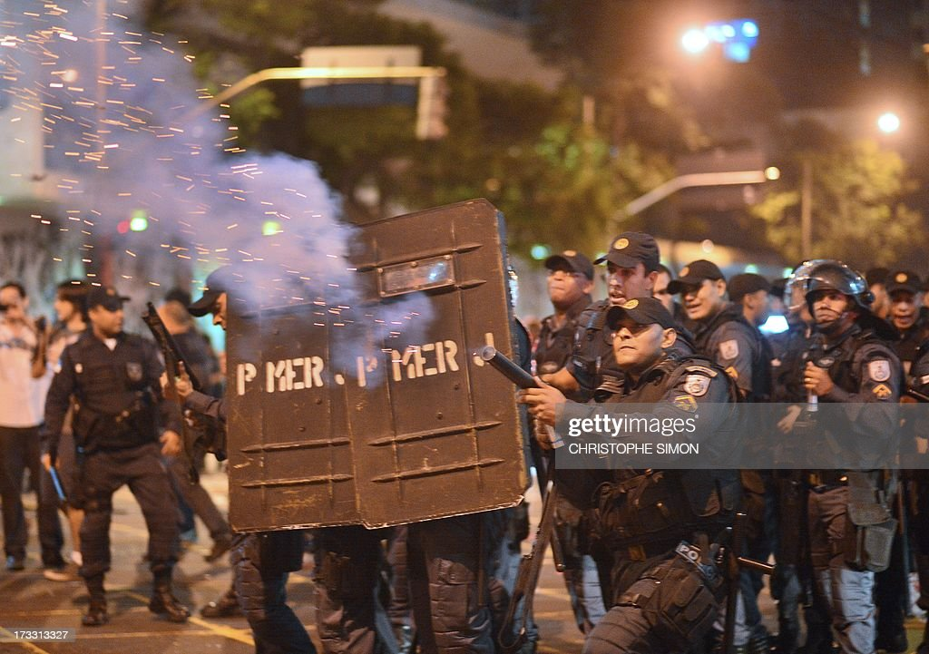 A riot police officer fires tear gas at violent demonstrators after clashes erupted following a march by Brazilian workers in Rio de Janeiro on July 11, 2013 in a day of industrial action called by major unions to press demands for better work conditions. Demonstrators on Thursday blocked roads and staged protest rallies across the country on the 'National Day of Struggles' which was called by the country's five leading labour federations during last month's mass street protests to demand better public services and an end to endemic corruption.