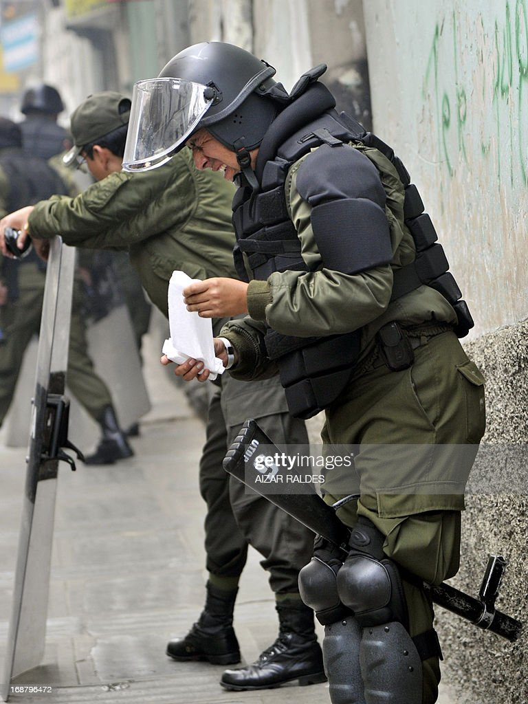 A riot police officer gestures after being affected by tear gas during clashes with workers protesting on the tenth day of an indefinite strike called by the Bolivian Workers' Centre (COB) to demand the government for a pension equivalent to 100% of their salaries, in the surroundings of the Plaza de Armas square in La Paz on May 15, 2013. AFP PHOTO / Aizar RALDES