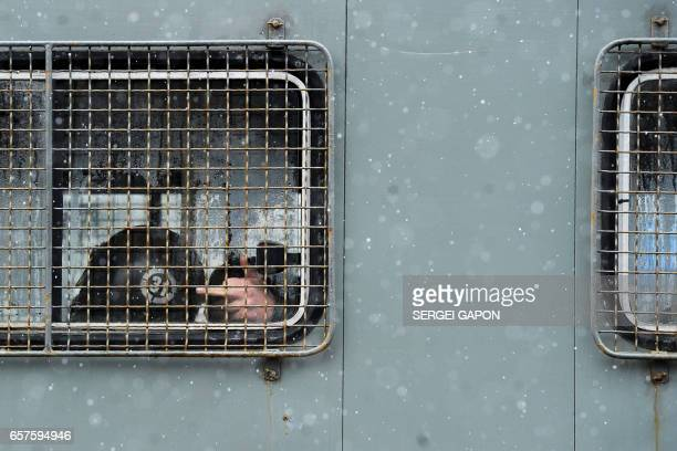 TOPSHOT A riot police officer gestures from a police van before an opposition rally against President Alexander Lukashenko's rule and a controversial...
