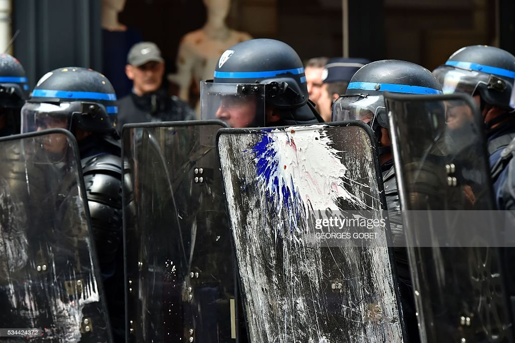 A riot police officer holds a shield covered in paint during a protest called by seven labour unions and students against labour and employment law reform on May 26, 2016 in Bordeaux, southwest France. Fresh rallies were due to be held May 26 in Paris and other cities in the latest bout of social unrest that started three months ago and has frequently turned violent. Under intense pressure, Prime Minister Manuel Valls vowed the labour law would not be withdrawn, but said it might still be possible to make 'changes' or 'improvements'. / AFP / GEORGES