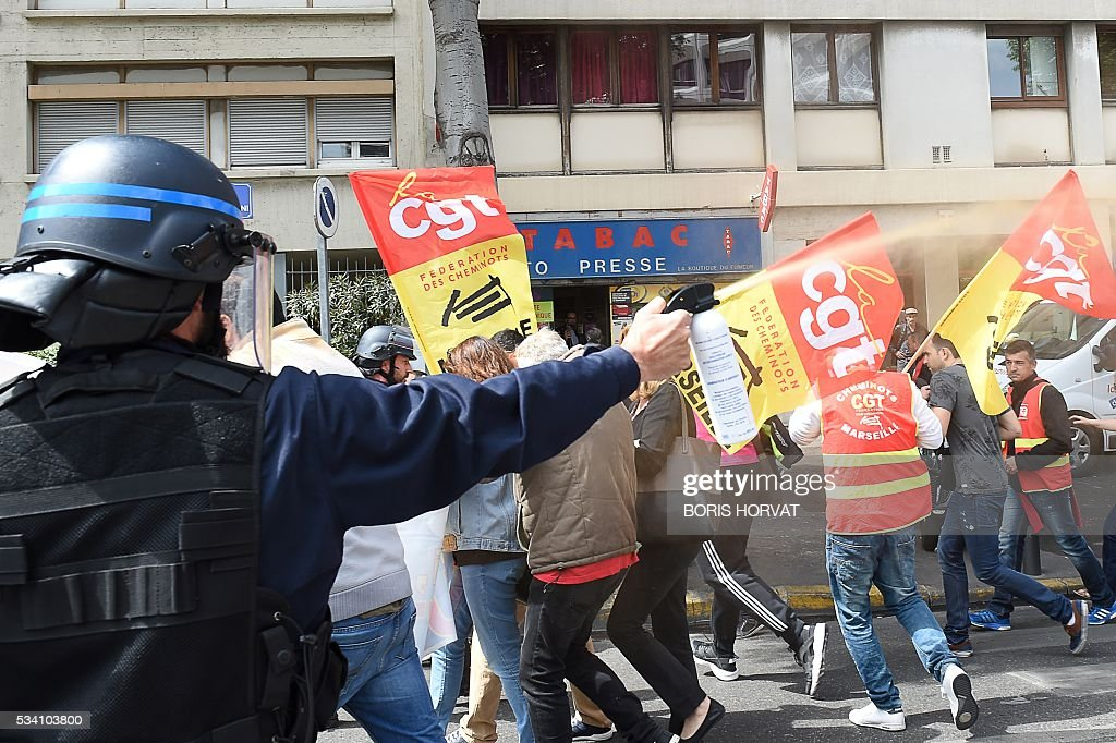 A riot police officer sprays pepper spray at unionists protesting against the government's proposed labour reform on May 25, 2016 in Marseille, southeastern France. / AFP / BORIS