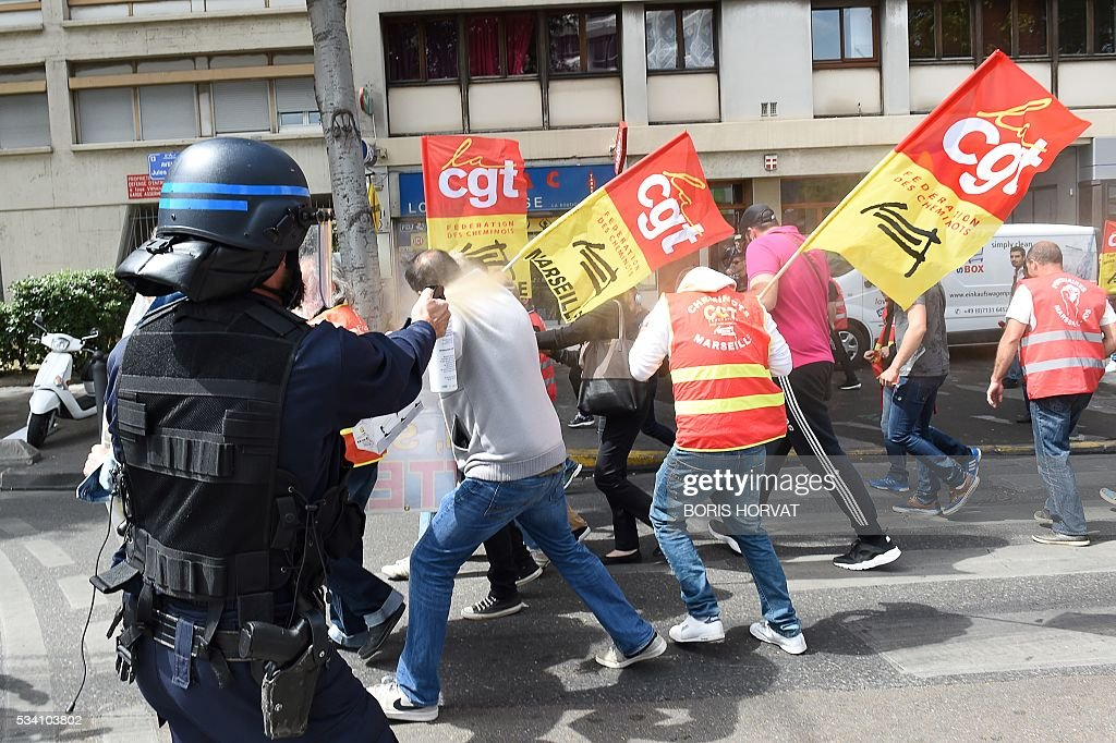 TOPSHOT A riot police officer sprays pepper spray at unionists protesting against the government's proposed labour reform on May 25 2016 in Marseille...