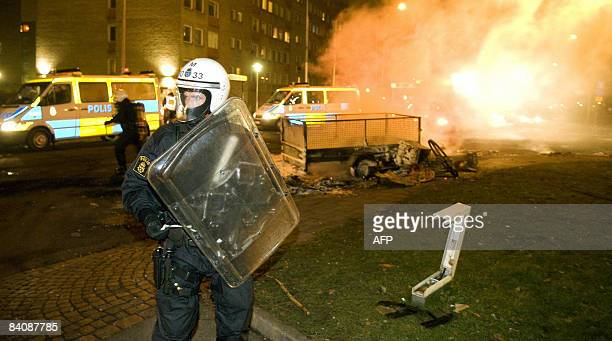 A riot police officer stands guard while colleagues extinguish burning barricades on the main road in the heavilyimmigrant populated neighborhood of...