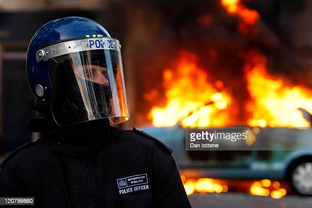 A riot police officer stands in front of a burning car during riots in Clarence Road Hackney on August 8 2011 in London England Pockets of rioting...