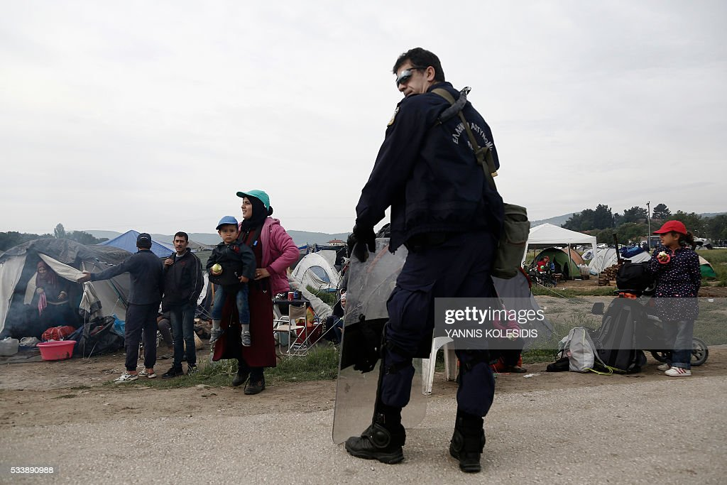 A riot police officer stands in front of refugees and migrants during an evacuation operation of a makeshift migrant camp at the border at the Greek-Macedonian border near the village of Idomeni, on May 24, 2016. In an operation which began shortly after sunrise on May 24, hundreds of Greek police began evacuating the sprawling camp which is currently home to 8,400 refugees and migrants, among them many families with children, an AFP correspondent said. At its height, there were more than 12,000 people crammed into the site, many of them fleeing war, persecution and poverty in the Middle East and Asia, with the camp exploding in size since Balkan states began closing their borders in mid February in a bid to stem the human tide seeking passage to northern Europe. / AFP / POOL / YANNIS