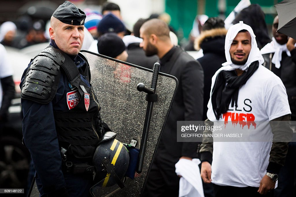 A riot police officer stands next to a protester on the Place de la Nation in Paris on February 9, 2016, during a demonstration by non-licensed private hire cab drivers, known in France as VTC (voitures de tourisme avec chauffeur or tourism vehicles with chauffeur). VTC drivers continued a fifth day of protests on February 9 against measures granted by the French prime minister to taxi drivers. / AFP / Geoffroy Van der Hasselt