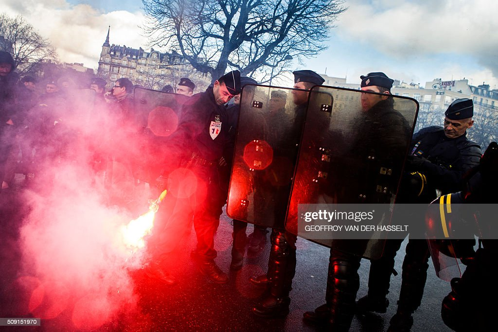 A riot police officer throws back a burning flare on the Place de la Nation in Paris on February 9, 2016, during a demonstration by non-licensed private hire cab drivers, known in France as VTC (voitures de tourisme avec chauffeur or tourism vehicles with chauffeur). VTC drivers continued a fifth day of protests on February 9 against measures granted by the French prime minister to taxi drivers. / AFP / Geoffroy Van der Hasselt
