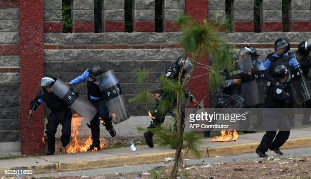 Riot police officers and members of the Cobra Special Unit trying to disperse students of the National Autonomous University of Honduras gathered...