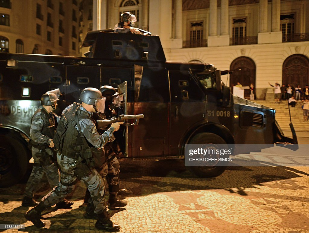 Riot police officers are deployed in Rio de Janeiro on July 11, 2013 after clashes erupted in parts of the city following a march by Brazilian workers in a day of industrial action called by major unions to press demands for better work conditions. Demonstrators on Thursday blocked roads and staged protest rallies across the country on the 'National Day of Struggles' which was called by the country's five leading labour federations during last month's mass street protests to demand better public services and an end to endemic corruption.