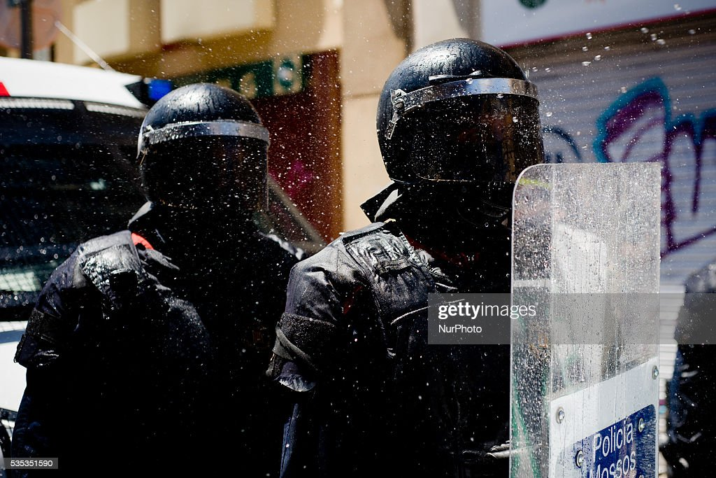 Riot police officers are impacted by water jets thrown by protesters attempting to access the area of the Banc Expropiat on 29 May, 2016 in Barcelona (Spain). Tense Sunday in the streets of the popular Gracia district of Barcelona. After the eviction of an occupied bank branch known as the Banc Expropiat (Expropiated Bank) on past Monday 23 riots have been happening following days. Today hundreds of protesters tried to enter the building again guarded by riot police officers.