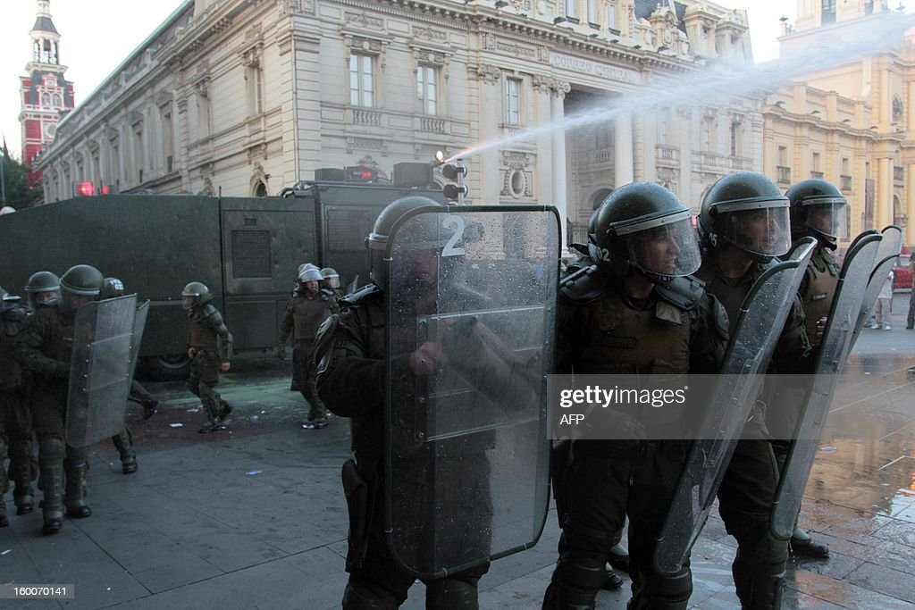 Riot police officers confront demonstrators during a march of the Peoples' Summit 'for Social Justice, International Solidarity and in Defence of the Commons', held in the sidelines of the weekend's CELAC-EU Summit, in Santiago on January 25, 2013. More than 40 Heads of State and Government of the Community of Latin American and Caribbean States (CELAC) and the European Union (EU) will meet on January 26 and 27 to promote a strategic partnership between the two regions. AFP PHOTO / RODRIGO SAENZ