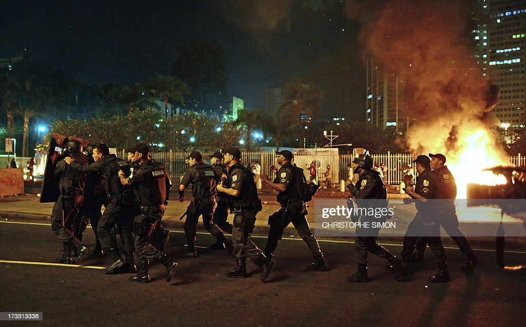 Riot police officers confront demonstrators during clashes which erupted following a march by Brazilian workers in Rio de Janeiro on July 11, 2013 in a day of industrial action called by major unions to press demands for better work conditions. Demonstrators on Thursday blocked roads and staged protest rallies across the country on the 'National Day of Struggles' which was called by the country's five leading labour federations during last month's mass street protests to demand better public services and an end to endemic corruption.