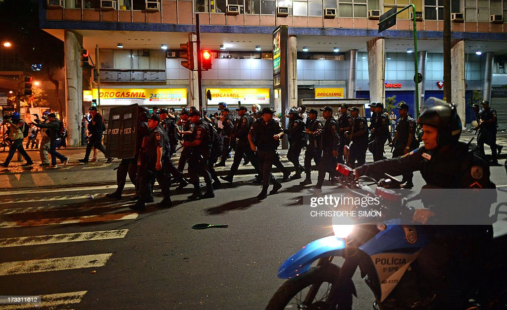 Riot police officers confront violent demonstrators after clashes erupted following a march by Brazilian workers in Rio de Janeiro on July 11, 2013 in a day of industrial action called by major unions to press demands for better work conditions. Demonstrators on Thursday blocked roads and staged protest rallies across the country on the 'National Day of Struggles' which was called by the country's five leading labour federations during last month's mass street protests to demand better public services and an end to endemic corruption. AFP PHOTO / CHRISTOPHE SIMON